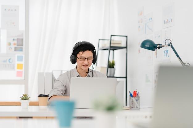 ホームオフィスで仕事をしながら、同僚とのビデオ通話の計画についてラップトッププレゼンテーションを使用してウイルス防止のための新しい通常の状況で社会的距離を隔てるアジア系のビジネスマン。コロナウイルス後のライフスタイル。 無料写真