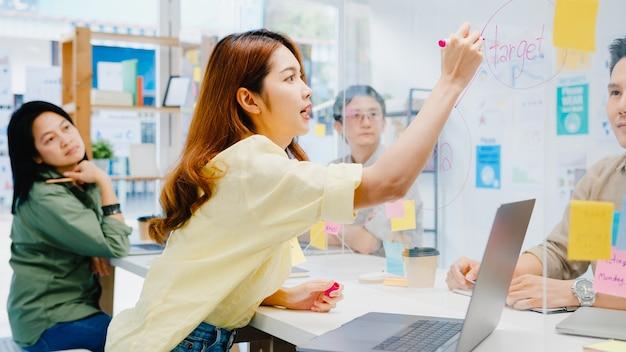 Азиатские бизнесмены, обсуждающие бизнес-встречу вместе, обмениваются данными и пишут на акриловой перегородке в новом обычном офисе. образ жизни, социальное дистанцирование и работа после коронавируса. Бесплатные Фотографии