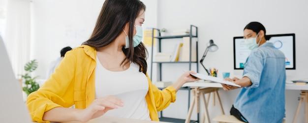アジアのビジネスマンは、ウイルスの予防とオフィスでの距離を保ちながら文書を渡すための新しい通常の状況での社会的距離を保つためにフェイスマスクを着用します。コロナウイルス後のライフスタイルと仕事。 無料写真