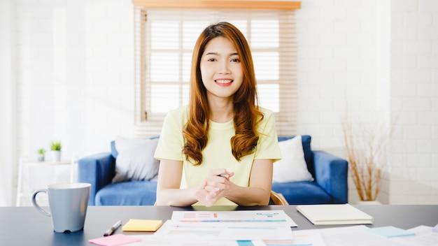 Азиатская деловая женщина, использующая компьютерный ноутбук, разговаривает с коллегами о плане видеозвонка, работая дома в гостиной. самоизоляция, социальное дистанцирование, карантин от вируса короны. Бесплатные Фотографии