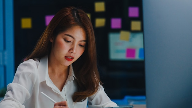 Asia businesswoman using computer talk to colleagues about plan in video call while working from home at living room at night. self-isolation, social distancing, quarantine for coronavirus prevention. Free Photo