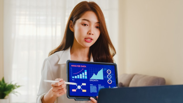 Asia businesswoman using laptop and tablet presentation to colleagues about plan in video call while working from home at living room. self isolation, social distancing, quarantine for coronavirus. Free Photo