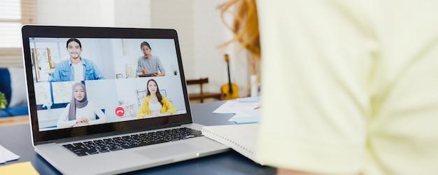 Азиатская деловая женщина с помощью ноутбука разговаривает с коллегами о плане видеозвонка, работая дома в гостиной. самоизоляция, социальное дистанцирование, карантин для предотвращения вируса короны. Бесплатные Фотографии