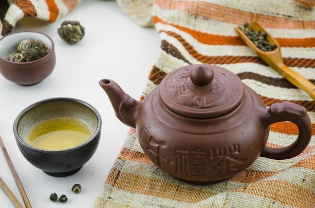 Asia culture fresh oolong tea and teapot on white backdrop Premium Photo