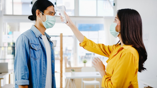 Asia female receptionist conducting wear protective face mask use infrared thermometer checker or temperature gun on customer's forehead before enter office. lifestyle new normal after corona virus. Free Photo