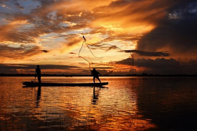 Asia fisherman net using on wooden boat casting net sunset or sunrise in the mekong river silhouette fisherman boat. Premium Photo
