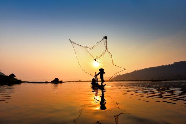 Asia fisherman net using on wooden boat casting net sunset or sunrise in the mekong river Premium Photo