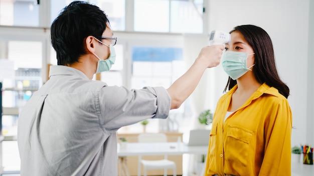 着用保護フェイスマスクを行うアジアの男性受付係は、オフィスに入る前に顧客の額に赤外線温度計チェッカーまたは温度ガンを使用します。コロナウイルス後の新しい正常なライフスタイル。 無料写真