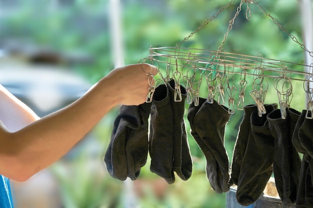 Asia teen is hanging the black sock on the clip for dry clothes after washing. Premium Photo