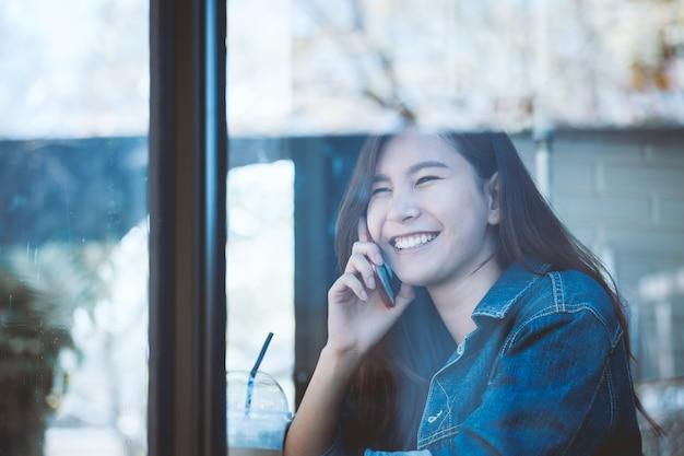 Азии подростков сидел один, используя сотовый телефон с улыбкой в кафе. Premium Фотографии
