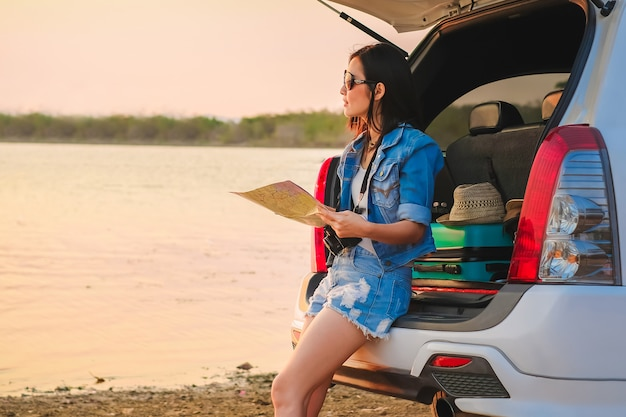 Asia traveler sitting on hatchback car and looking at map when sunset Premium Photo