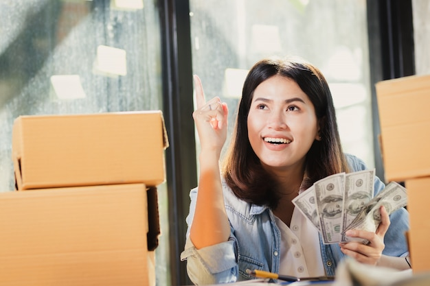 Asia woman holding us dollar banknotes money smiles with happy. Premium Photo