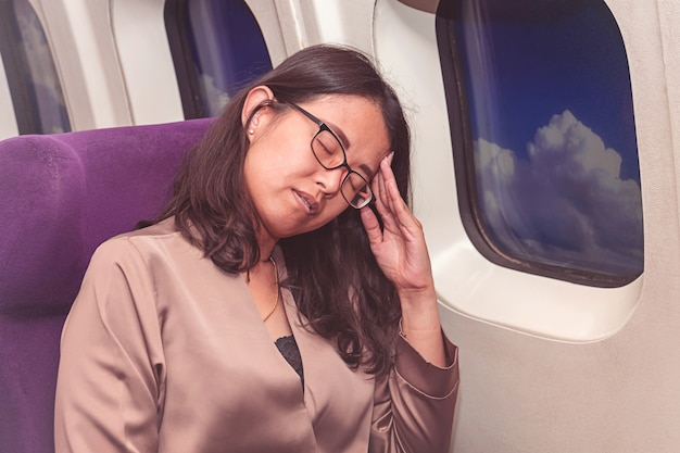 Asia woman suffer from headache inside airplane Premium Photo