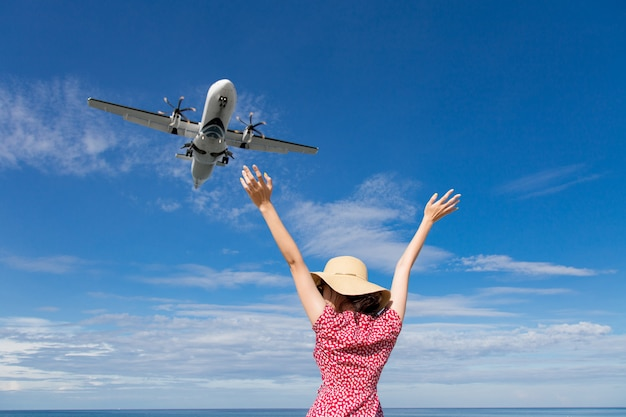 Asia woman traveling looking at the flying plane above the sea Premium Photo