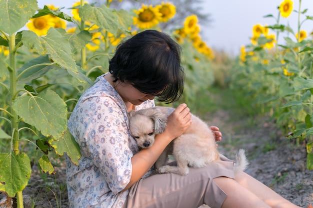 Asia women hugging dog travel at sunflower meadow Photo | Premium