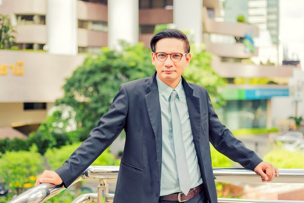 Asia young business man in front of the modern building in downtown Premium Photo
