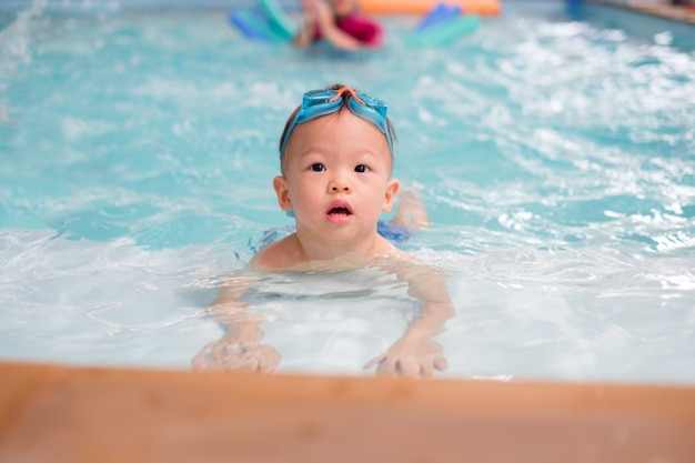 Asian 1 year old toddler boy child wear swimming goggles learn to swim Premium Photo