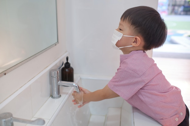 Asian 3 - 4 years old toddler boy child wearing protective medical mask washing hands by himself on sink in public toilet for kids, sanitation concept - soft & selective focus Premium Photo