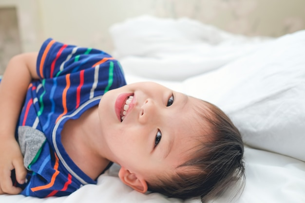 Asian 3 - 4 years toddler boy child waking up in bed, cheerful kid lying on bed looking at camera Premium Photo