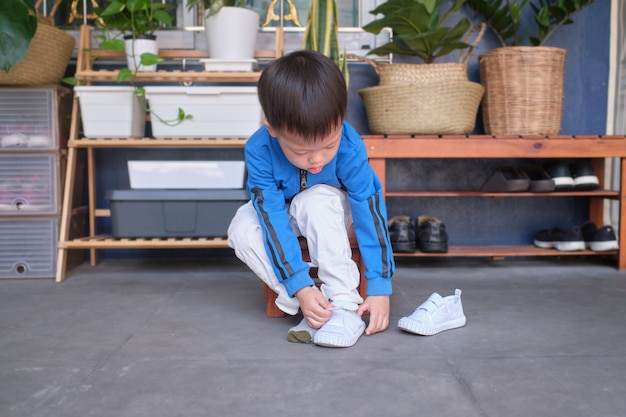 Asian 3 years old toddler kindergarten kid sitting near shoe rack near front door of his house and concentrate on putting on his white shoes / sneakers Premium Photo