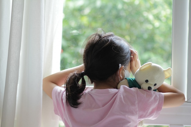 Premium Photo   Asian 6 or 7 years old kid wearing medical mask.little girl  standing by the window and looking outside.she look sad,bored.she may sick  or quarantine from the coronavirus disease 19 (
