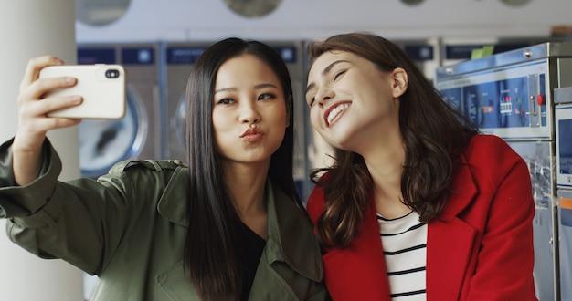 ランドリーサービスでselfie写真を撮りながら笑顔とスマートフォンのカメラにポーズをとってアジアと白人の若い美しい女の子。洗濯機で携帯電話で自分撮り写真を作るきれいな女性。 Premium写真