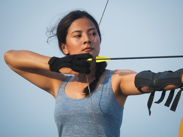 Asian archery woman with bow shooting on the beach Premium Photo