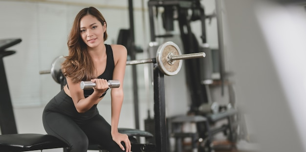 Asian athletic woman holding dumbbell and smiling at the camera Premium Photo
