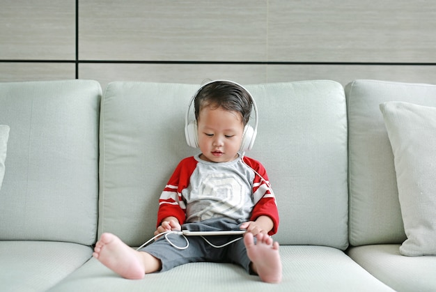 Asian baby boy sitting on sofa and listening music at headphones Premium Photo