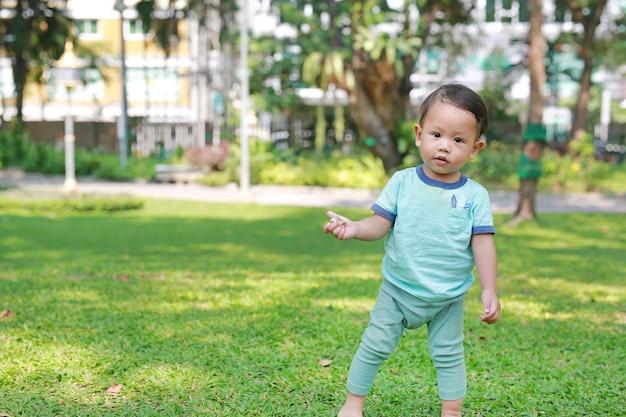 Первый шаг азиатского ребёнка идя на сад зеленой травы. Premium Фотографии