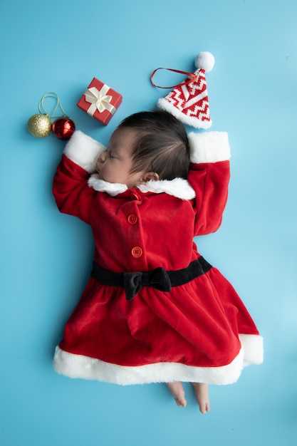 Asian baby newborn on santa claus uniform sleeping with red box present and red hat on blue background Premium Photo