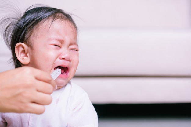 アジアの赤ちゃんが病気ですが、copyspaceで注射器で薬を食べることを拒否します Premium写真