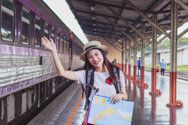 Asian backpack traveler woman holding generic local map and waving ...