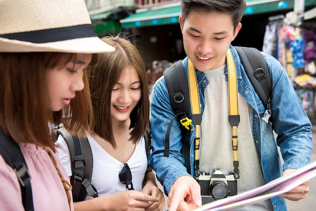 Asian backpacker friends looking at the map while traveling in bangkok thailand Premium Photo