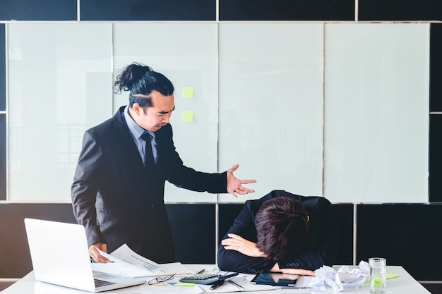 Asian bad angry boss yelling at business man sad depressed employee reprimand Premium Photo