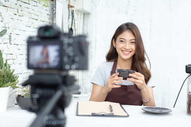 Asian barista looking to camera for live to social media Premium Photo