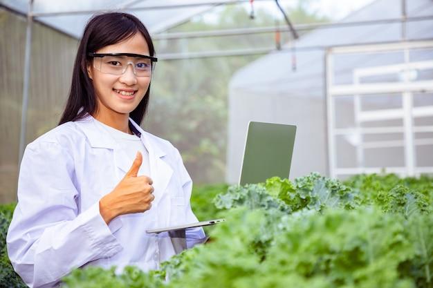 有機農場でケール種の野菜を研究するためにラップトップを使用しているアジアの美しいバイオテクノロジー。 Premium写真