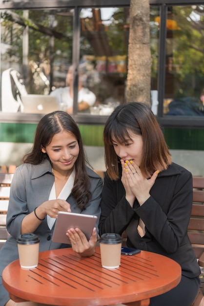 Asian  beautiful business woman working with tablet and smartphone in coffee cafe shop Premium Photo