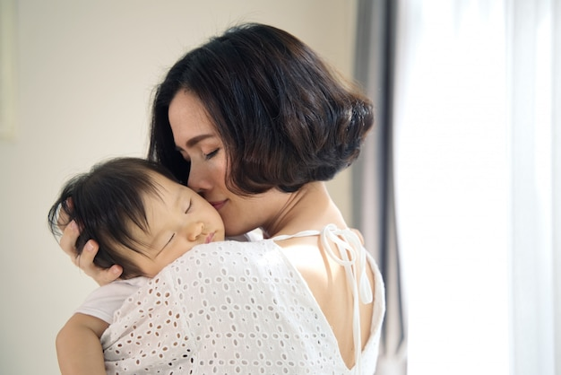 Asian beautiful mother hugging sleeping baby in her arms and kissing the kid gently. the mom closing her eyes while holding her baby head to rest on shoulder. touch of love and family relationship. Premium Photo