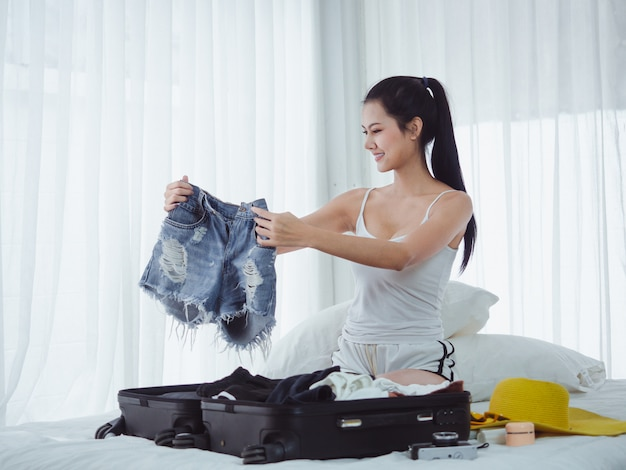 Asian beautiful woman are preparing bags to go on holiday Premium Photo