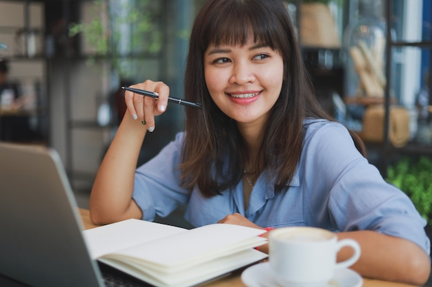 Asian beautiful woman  in blue shirt  using laptop and drinking coffee Premium Photo