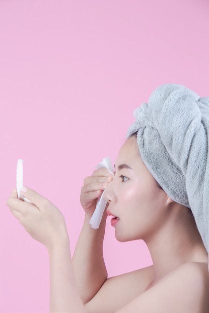 Asian beautiful woman cleans the face on a pink background. Free Photo