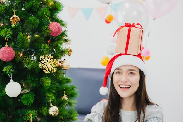 Asian beautiful woman is decorating christmas tree in white room with gift box placed on the head.smiling face and happy to celebrate festivel new year holiday. Premium Photo