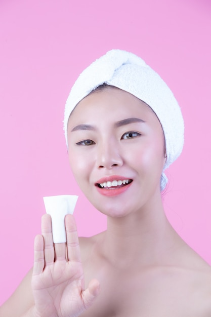 Asian beautiful woman wiping the face on a pink background, cosmetology and spa . Free Photo