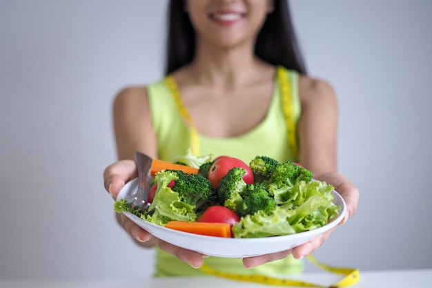 Asian beautiful women are happy to eat salad vegetables. Premium Photo