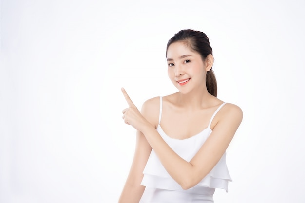 Asian beautiful young woman pointing one hand with finger on upper side with smile face Premium Photo