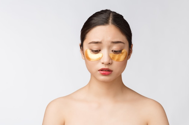 アジアの美しさの10代の女性が心配して目の下のゴールドのアイマスクパッチで彼女の肌をケアします。 Premium写真
