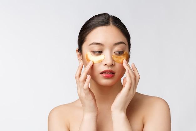 アジアの美しさの10代の女性は目の下の金のアイマスクパッチで彼女の肌をケアします。 Premium写真