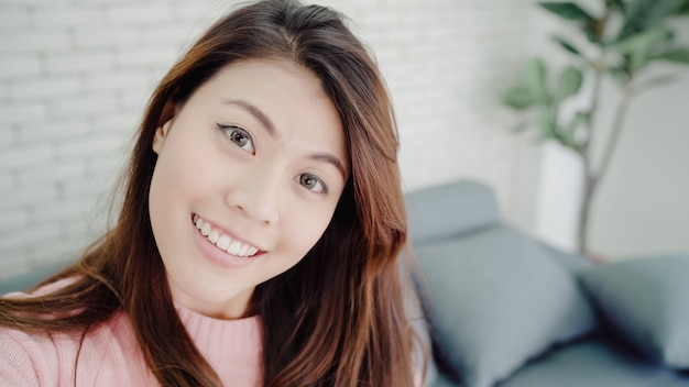 Asian blogger woman using smartphone recording vlog video in living room at home Free Photo