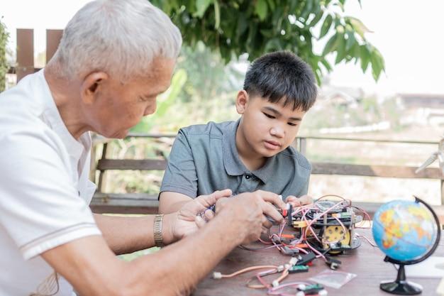 アジアの少年と引退した祖父が新しいロボット技術のプログラミングプロセスを学ぶ Premium写真